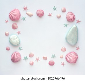 Summer time concept with painted pink and blue sea shells, starfish and stones on a white surface. Flat lay. Top view.  . Frame of shells and starfish.