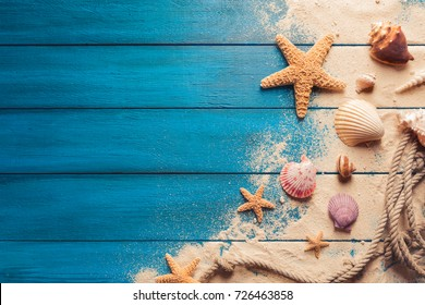 Summer time concept with sea shells and starfish on a blue wooden background and sand - Shutterstock ID 726463858