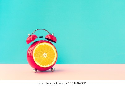Summer time concepts ideas with orange alarm clock on blue pastel background.