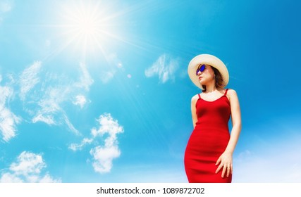 Summer time concept.Woman with sunglasses and sun hat in red dress on hot summer day with blue sky background and sun.