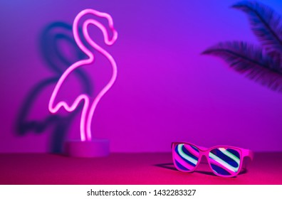 Summer time with flamingo,palm leaf,sunglasses refection neon pink and blue and green light on table with copy space.Trendy vacation holiday background