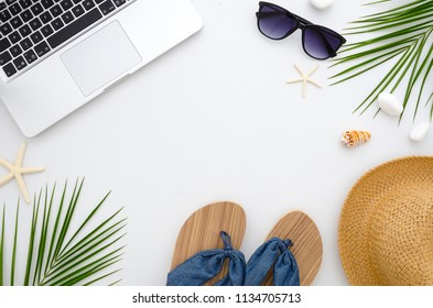 Summer time flat lay. Work and travel concept. Frame from laptop, green leaves, flip flops, sunglasses and straw hat.