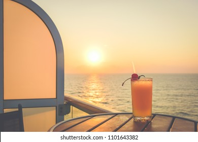 Summer time holiday concept: Refreshing cocktail on a cruise vacation, with stunning sunset view.