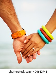 Summer time image of a couple holding hands. The groom with the bride in his arms. Wearing stylish watch and colored bracelets, and diamond engagement ring on her finger.