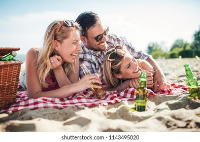 Summer time. Lucky man enjoys in a good mood with two beautiful girls on the beach. Lifestyle, vacation, relationships concept