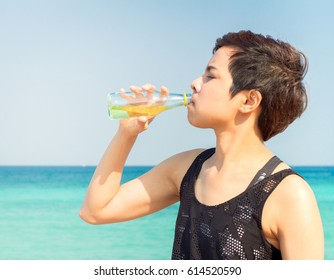 Summer time, portrait Fitness woman drinking water after fitness exercise at beach, drinks Energy Drink