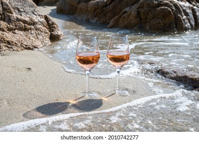 Summer time in Provence, two glasses of cold rose wine on sandy beach near Saint-Tropez in sunny day, Var department, France