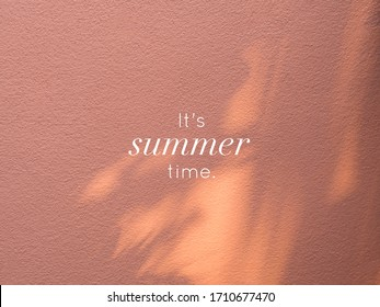 It's summer time. Quote on wall peach color with shadows of trees, summer concept