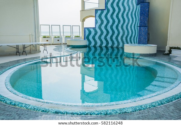 Summer time. round outdoor empty swimming pool. In the hotel to rest. Tropical terrace with swimming pool and beautiful view to the sea. interior background.