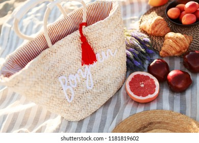 Summer time at the sea. Picnic on the beach - croissants, apples , strawberries and sweets.  Trendy straw bag.