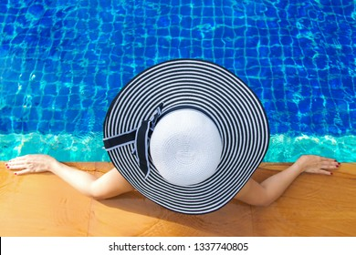 Summer time and Vacations. Women lifestyle relaxing and happy near luxury swimming pool sunbath, summer day at the beach resort in the hotel. Summer Concept