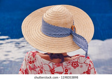 Summer time. Woman with hat and blue water background. Relaxing