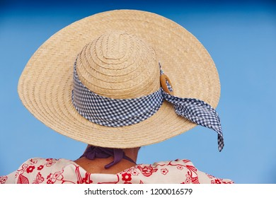Summer time. Woman with straw hat. Blue background. Relaxing time