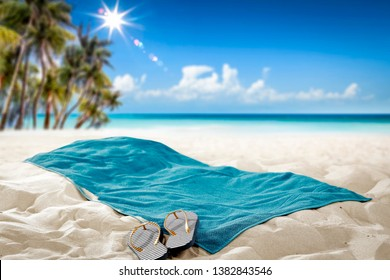 Summer towel on sand. Beach background with palms and ocean. Free space for your decoration.