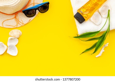 Summer travaling to the sea with straw hat, sun glasses, sunblock lotion on yellow background top view mock up