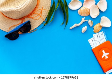 Summer travaling to the sea with straw hat, sun glasses, tickets and passport on blue background top view mock up