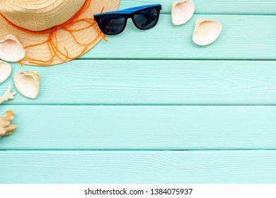 Summer travaling to the sea with straw hat, sun glasses, shells on mint green wooden background top view mock up