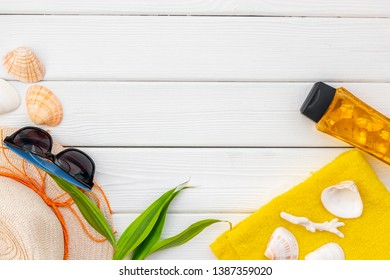 Summer travaling to the sea with straw hat, sun glasses, sunblock lotion on white wooden background top view mock up