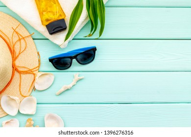 Summer travaling to the sea with straw hat, sun glasses, sunblock lotion on mint green background top view mock up