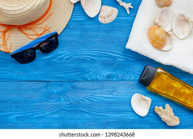 Summer travaling to the sea with straw hat, sun glasses, sunblock lotion on blue wooden background top view mock up