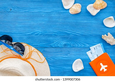 Summer travaling to the sea with straw hat, sun glasses, tickets and passport on blue wooden background top view mock up