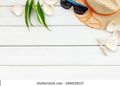 Summer travaling to the sea with straw hat, sun glasses, shells on white wooden background top view mock up