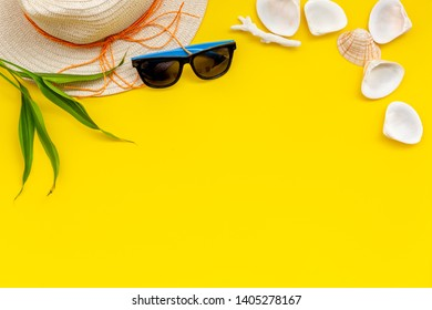 Summer travaling to the sea with straw hat, sun glasses, shells on yellow background top view mock up