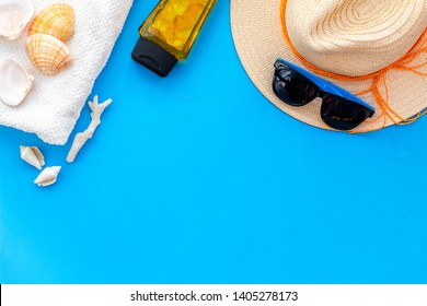 Summer travaling to the sea with straw hat, sun glasses, sunblock lotion on blue background top view mock up