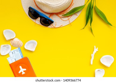 Summer travaling to the sea with straw hat, sun glasses, tickets and passport on yellow background top view mock up