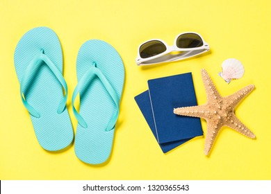 Summer travel background. Blue flip flops, sunglasses, passport and starfish on yellow background. Top view.