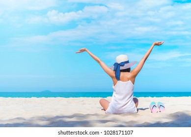 Summer travel background concept. Happiness woman siting on beach raise hands up to blue sky. Hello vacation. Picture for add text message. Backdrop for design art work.