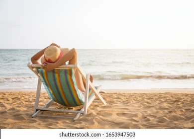 Summer travel beach vacation concept, Traveler asian woman with straw hat relax on chair beach at Koh Mak, Trad, Thailand