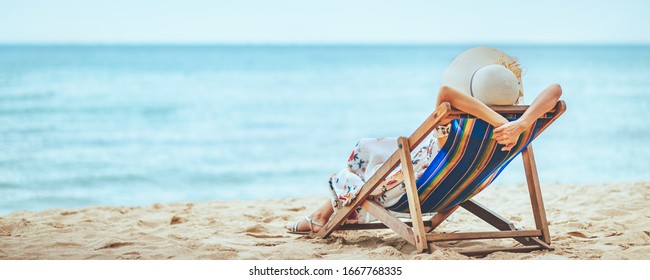Summer travel beach vacation concept, Traveler asian woman with hat and dress relax on chair beach at Pattaya, Chon Buri, Thailand