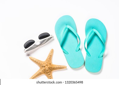 Summer travel concept. Flip flops, sunglasses and starfish on white. Top view.