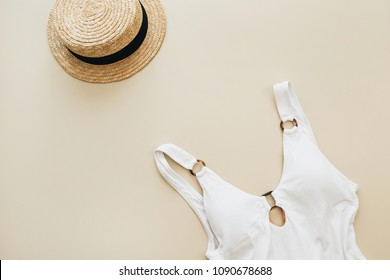 Summer travel fashion composition. Women's swimsuit, straw on pastel beige background. Flat lay, top view minimal clothes concept.