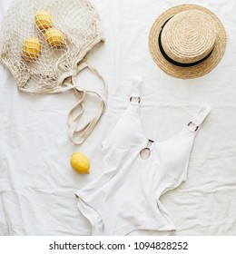 Summer travel fashion composition. Women's swimsuit, straw and lemons in string bag on linen background. Flat lay, top view minimal clothes concept.