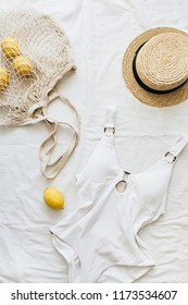 Summer travel fashion composition. Women's swimsuit, straw, lemons in string bag on linen. Flat lay, top view minimal clothes concept.