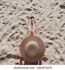 Summer travel fashion and vacation concept. Beautiful young, tanned woman with a straw hat is lying and relaxing on tropical beach with white sand showing legs. Top view, flat lay.