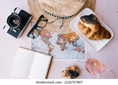 Summer travel flat lay: world map, vintage film camera, croissant, a glass of rose wine, wicker beach hat, paper notepad, glasses on the pink wooden table background, top view