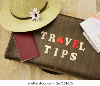 """Summer travel hat,flower,old suitcase,brown passport,map and wooden letters: """"travel tips"""""""