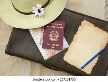 Summer travel hat,flower,old suitcase,Italian passport,map and travel checklist with free space for a text.
