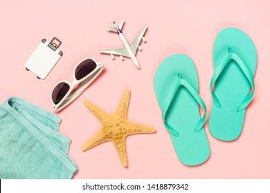 Summer travel holiday flat lay background on pink. Blue flip flops, sunglasses and starfish.