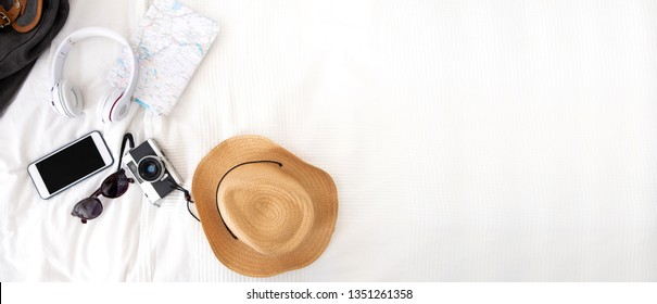 Summer travel items on blanket on bed.Top view of accessories travel (camera,hat,headphone,map ) on bed blankket.prepareing for holiday vacation trip.journey planning.banner for display of design