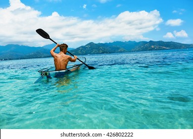 Summer Travel Kayaking. Man Paddling Transparent Canoe Kayak In Tropical Ocean, Enjoying Recreational Sporting Activity. Male Canoeing With Paddle, Exploring Sea On Vacation. Rowing Water Sports