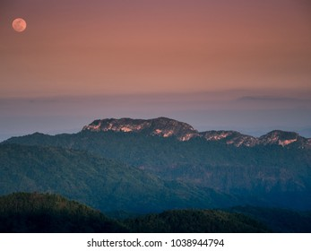 summer travel and landscape concept from sunlight on mountain with moon and blue sky background
