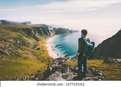 Summer travel man tourist standing alone on mountain top over ocean beach active lifestyle hiking adventure vacations in Norway outdoor