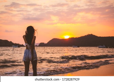 Summer travel vacation concept, Happy traveler asian woman with white bikini and shorts jeans relax and walk on sea beach in sunset at Koh Mak, Thailand