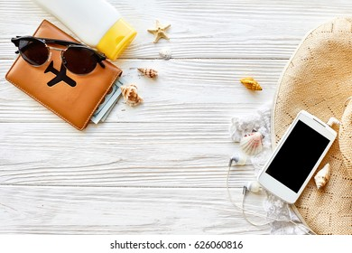 summer travel vacation concept, space for text. passport money phone with empty screen and sunglasses and sunscreen shells hat on white wooden background. hello summer. wanderlust