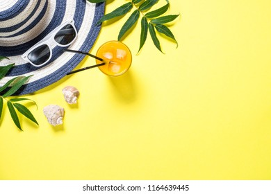 Summer travel vacation concept.  Striped hat, drink, sunglasses and tropical leaves on yellow background. Top view with copy space.