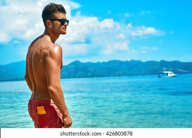 Summer Travel Vacation. Handsome Man With Sexy Body In Fashionable Sunglasses Sunbathing, Tanning At Sea Beach. Fitness Male Model With Sunscreen Lotion, Sun Block Skin Protection Cream In Pocket